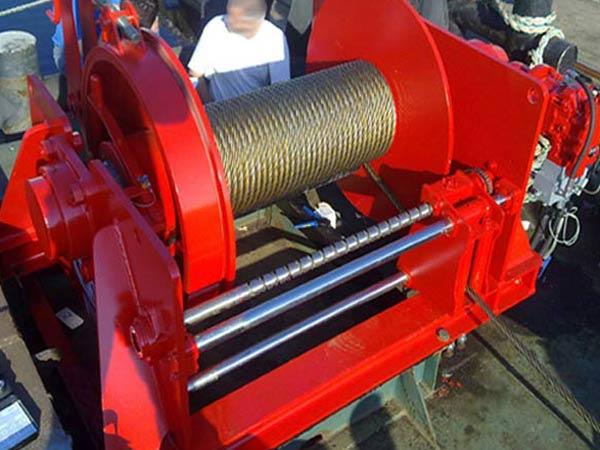 Cabrestante de tracción de cable con dispositivo de bobinado